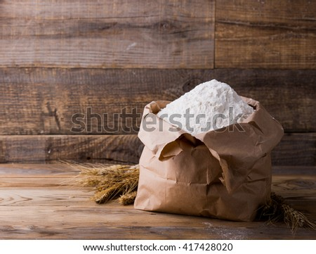 Wheat flour in Kraft paper bags. Paper packaging is on wooden background. - stock photo