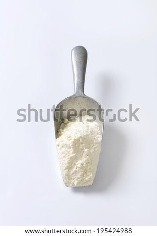 wheat flour on the measuring spoon - stock photo