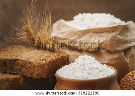 Wheat flour, sliced bread, wheat ears on an old wooden background - stock photo