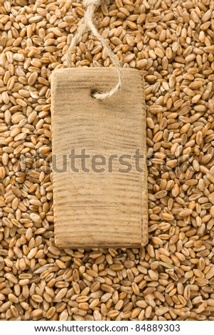 wheat grain and price tag with wood - stock photo