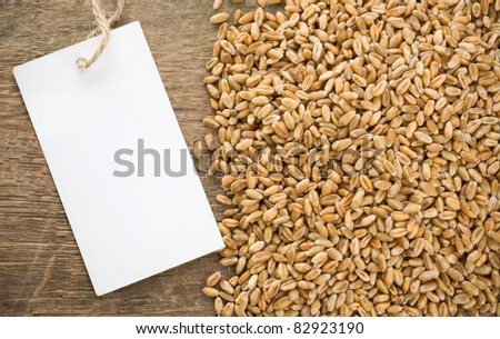 wheat grain and tag price on wood - stock photo