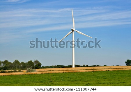 wheat harvest with combine harvester and wind turbine generating electricity - stock photo