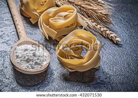 Wheat rye ears wooden spoon flour raw spiral pasta fettuccine on black background. - stock photo
