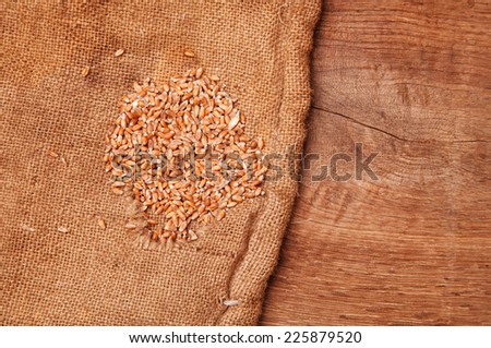 wheat seeds in a canvas sack on a wooden desk - stock photo