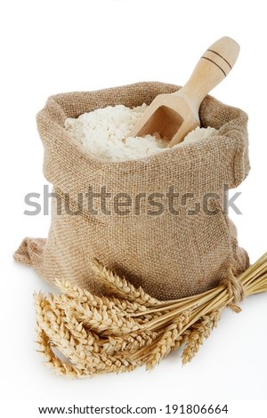 Wheat spike and flour in burlap bag on white background
