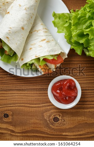 wheat tortilla with chicken and vegetables on plate on wooden table