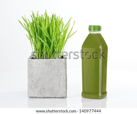 Wheatgrass and a bottle of fresh green juice, on white background. - stock photo