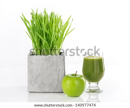 Wheatgrass, apple and a glass of fresh green juice, on white background. - stock photo