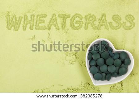 Wheatgrass. Green food supplement. Word wheatgrass written in green ground powder, top view. Healthy lifestyle. - stock photo
