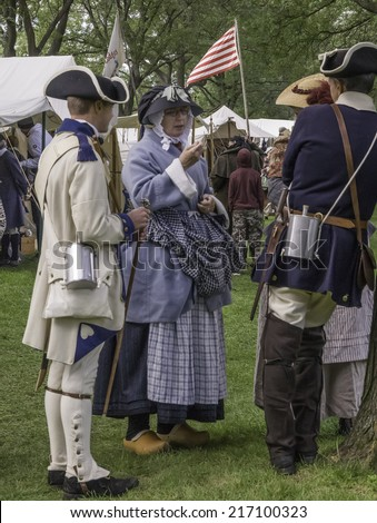 WHEATON, ILLINOIS/USA - SEPTEMBER 13, 2014: An unidentified woman in period dress socializes with compatriot actors in a military camp at a reenactment of the American Revolutionary War (1775-1783).