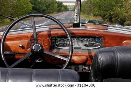 Wheel and dashboard of a old car - stock photo