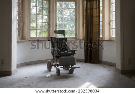 wheel chair by windows in old abandoned hospital - stock photo