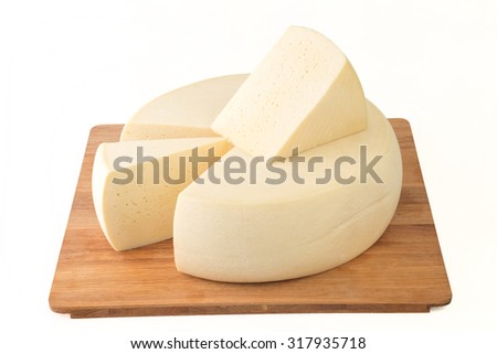 Wheel hard cheese and two triangular pieces on wooden tray. - stock photo