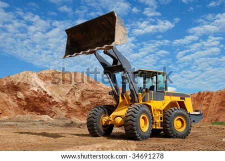 wheel loader bulldozer with fully raised bucket over blue cloudy sky standing in sandpit - stock photo