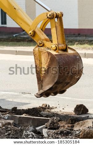 wheel loader excavator digging deep trench on sandy rocky land - stock photo