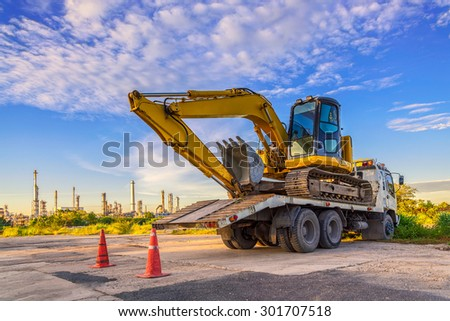 Wheel loader excavator machine  cars park on the truck at the construction site - stock photo