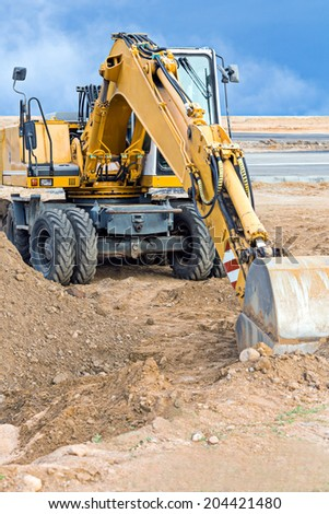Wheel loader excavator parked at construction site - stock photo