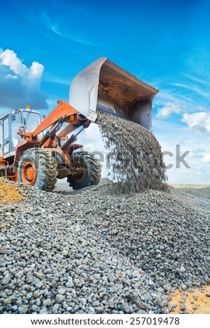 wheel loader excavator pouring gravel from scoop - stock photo