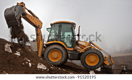 Wheel loader Excavator with backhoe digging trench and unloading land