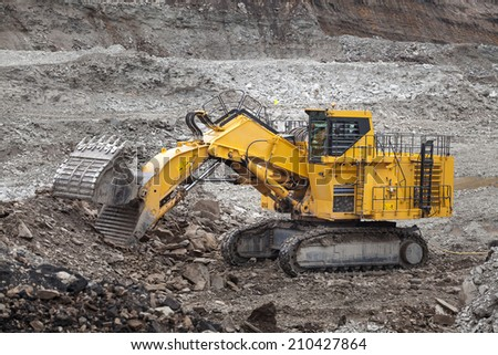 Wheel loader excavator with backhoe unloading clay - stock photo