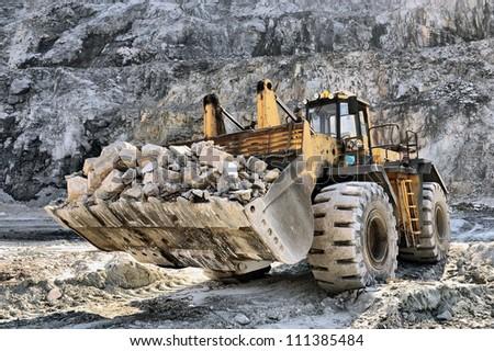 macchine speciali allestimento acciaieria altofornoed affini Stock-photo-wheel-loader-machine-unloading-rocks-in-the-open-mine-of-iron-ore-111385484
