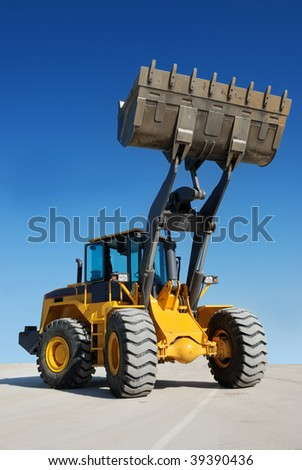 wheel loader over white with fully raised bucket (in focus) - stock photo