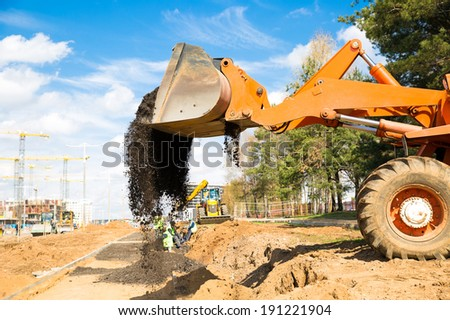 Wheel loader unloading crushed asphalt - stock photo