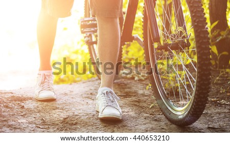 Wheel of a bicycle close up and running male legs - stock photo