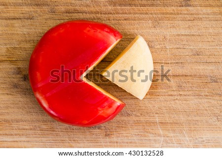Wheel of fresh gouda cheese with a red rind and a single wedge portion cut out, peeled and separated to the side on a wooden cutting board