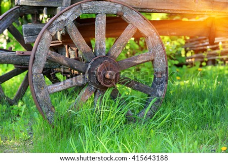 wheel of old wooden carriage in green grass - stock photo