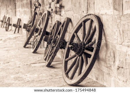 Wheel of Time. Vintage Black and White Picture of old wooden wheels on a castle in Bavaria, Germany / Europe . Still Life Picture. Stone walls. - stock photo