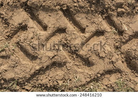 Wheel's trail tread in the red mud as a background - stock photo