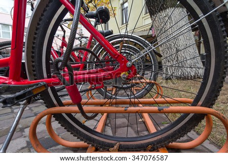 Wheel stoyaschik parked bicycle closeup. Urban transport