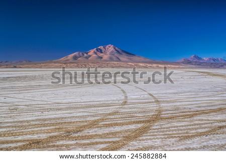 Wheel tracks in desert covered by white salt in Salar de Uyuni in Bolivia - stock photo