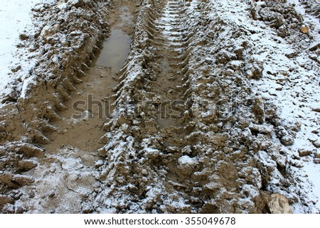 Wheel tracks on dirt and snow