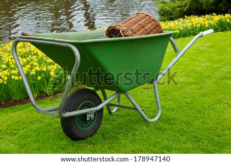 Wheelbarrel containing gardening tools standing on freshly mown lawn - stock photo