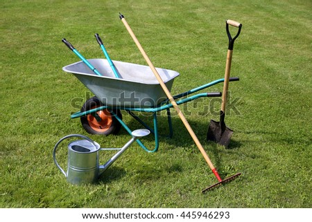 Wheelbarrow and gardening tools on green grass