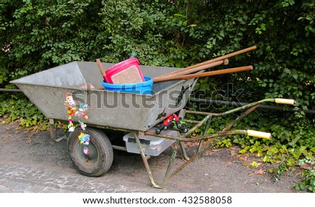 Wheelbarrow and lost pacifiers at park. Wheelbarrow and work tool in the garden with a bunch of pacifiers found in Berlin zoo garden.   - stock photo