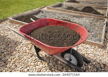Wheelbarrow full of compost dirt sitting in a backyard garden ready to help grow healthy vegetables - stock photo