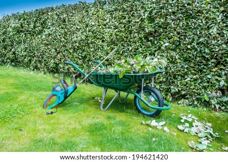 Wheelbarrow full of leaves and hedge trimmer