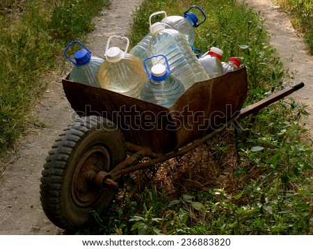 wheelbarrow full of plastic bottles with artesian water - stock photo
