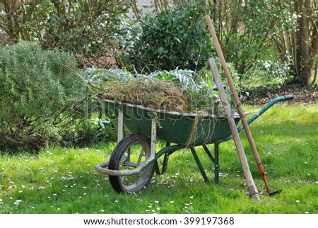 wheelbarrow full with garden weeds and tools in a garden