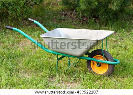 Wheelbarrow. Garden tools on a green lawn.