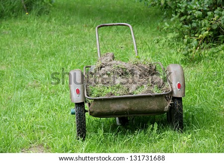 Wheelbarrow loaded by a ground on a lawn
