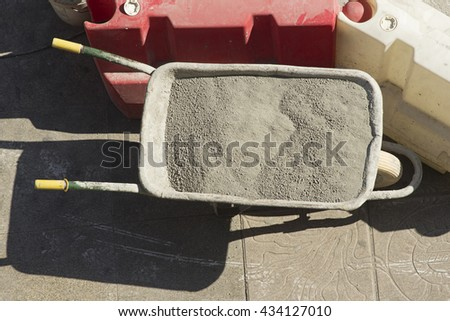 wheelbarrow of construction charged with  concrete, cement,  for repairing sidewalk  in street city - stock photo