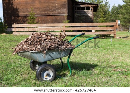 Wheelbarrow with dry leaves standing in rural backyard near the wooden house - stock photo