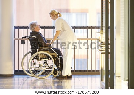 Wheelchair and patient in hospital with nurse - stock photo