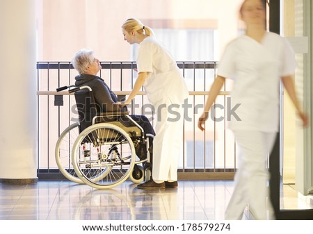 Wheelchair and patient in the hospital with nurses - stock photo