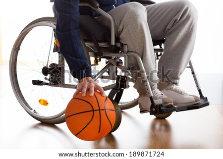 Wheelchair basketball player in sportswear dribbling the ball - stock photo