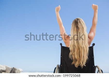 Wheelchair bound blonde sitting on the beach with arms up on a sunny day - stock photo